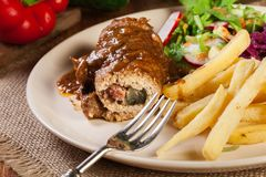 Pork roulade with french fries with salad. On a plate Royalty Free Stock Photography