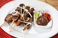Pork satay. A shot of pork satay dish on white plate royalty free stock photo