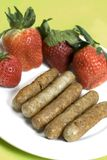 Pork sausage links with strawberries Royalty Free Stock Photo