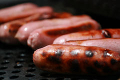Pork sausages on a barbecue. Pink pork sausages on a BBQ Royalty Free Stock Photography