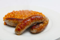 Pork sausages and beans. British pork sausages and baked beans on a white plate royalty free stock photo