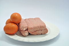 Pork sausages with eggs. A plate of raw pork sausages with three hen eggs on a white plate Royalty Free Stock Image