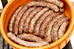 Pork sausages in a row clay casserole Stock Photos