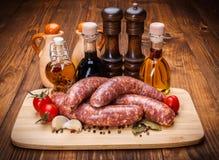 Pork sausages with spicy oil bottles. Pork sausages on cutting board with spicy oil bottles stock photos