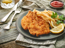Pork schnitzel and fried potatoes Stock Photo