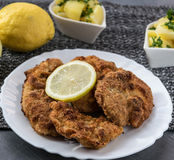 Pork schnitzel with lemon and diced potatoes royalty free stock photos