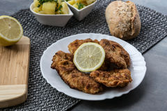 Pork schnitzel with lemon and diced potatoes royalty free stock images