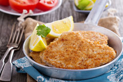 Pork schnitzel with parmesan. Pork schnitzel with lemon wedges in pan Stock Images
