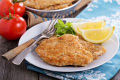 Pork schnitzel with parmesan. Pork schnitzel with lemon wedges in pan Royalty Free Stock Photography