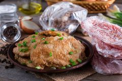 Pork schnitzel in a plate and frozen pork neck chops meat. On wooden desk stock photo