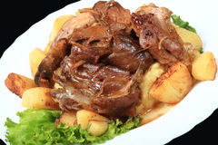 Pork Shank. With fresh potatoes in the oven Royalty Free Stock Images