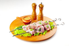 Pork shish kebab. With seasoning on the woody plate Stock Image