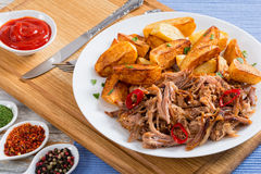 Pork shoulder grilled in oven with fried potato wedges Royalty Free Stock Photo