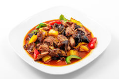 Pork, Sichuan sauce, pepper, garlic, Chinese wood mushrooms. In a white plate on a white background stock photography