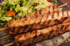 Pork skeewers. Barbequed pork skeewers on a stoneplate Royalty Free Stock Photos