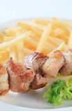 Pork skewer with French fries Stock Photos
