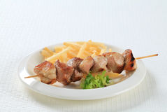 Pork skewer with French fries Royalty Free Stock Photo