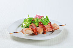 Pork skewer with salad greens Stock Photography