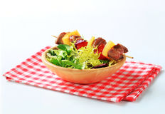 Pork skewer and spring salad mix Stock Images