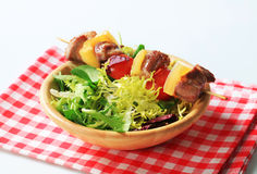 Pork skewer and spring salad mix Stock Image