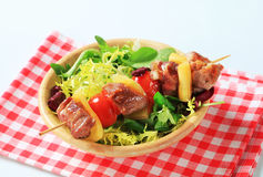 Pork skewer and spring salad mix Royalty Free Stock Photos