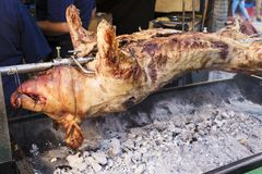 Pork skewered on an iron cooking on coals. Pork skewered on an iron cooking on some embers in a market on the street royalty free stock photo