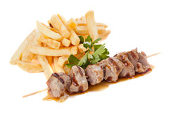 Pork  skewers with french fries Stock Photos