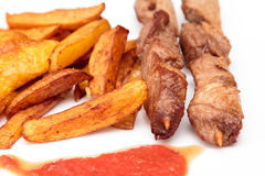 Pork skewers and French fries Stock Photos