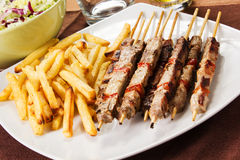 Pork skewers with french fries Royalty Free Stock Image