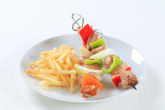Pork skewers with fries Royalty Free Stock Image
