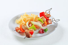 Pork skewers with fries Stock Image