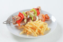 Pork skewers with fries Stock Photos