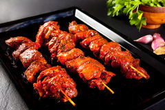 Pork skewers to grill and barbecue. Still life on black background Royalty Free Stock Photos