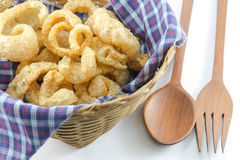 Pork snack, Pork rind, Pork scratching or pork crackling in basket with wood spoon and fork Stock Photo