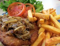 Pork Schnitzel. Topped with fried onions, served with French fries, and garnished with lettuce and tomatoes stock images