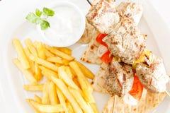 Pork Souvlaki. On pita bread with tomato, onion & tzatziki royalty free stock photo
