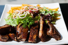 Pork spare ribs with salad and French Fries Stock Photo