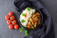 Pork in spicy curry sause with eggplant and green beans, served with cooked rice in a black metal bowl on a grey Royalty Free Stock Images