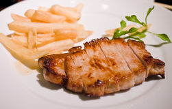 Pork Steak. Grilled pork steak served with french fries on white plate Royalty Free Stock Photo
