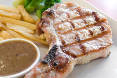Pork Steak. Grilled pork steak served with french fries and gravy sauce on white plate Stock Photo