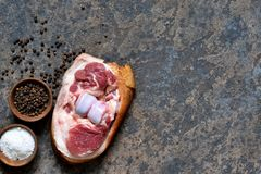 Pork steak with bacon with salt and pepper on the kitchen stone table. View from above. Pork steak with bacon with salt and pepper on the kitchen stone table stock photo
