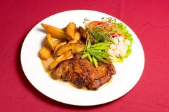 Pork steak with baked potatoes Royalty Free Stock Photo