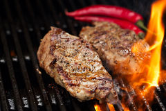 Pork steak on bbq grill with flame Royalty Free Stock Images