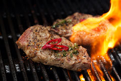 Pork steak on bbq grill with flame Stock Image