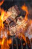 Pork steak on bbq grill with flame Royalty Free Stock Photos