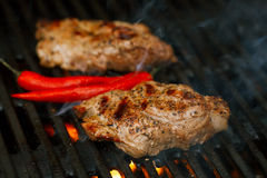 Pork steak on bbq grill with flame Stock Photos