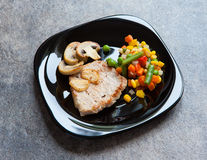 Pork steak on a black plate. With vegetables Stock Photo