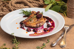 Pork steak on the bone with cherry-ginger sauce. Concept: restaurant menus, healthy eating, homemade, gourmands, gluttony. Pork steak on the bone with cherry royalty free stock image