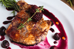 Pork steak on the bone with cherry-ginger sauce. Concept: restaurant menus, healthy eating, homemade, gourmands, gluttony. Pork steak on the bone with cherry stock photography