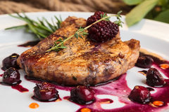 Pork steak on the bone with cherry-ginger sauce Royalty Free Stock Photography